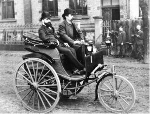 Foto en blanco y negro de un Benz motor-wagen de 1886 con dos hombres encima