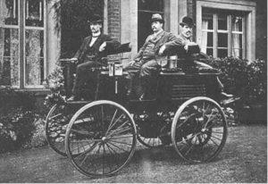 Foto en blanco y negro de un coche eléctrico de 1884 de Thomas Parker con 3 personas encima